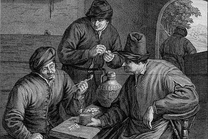 Three men indoors round an inn table with drink...